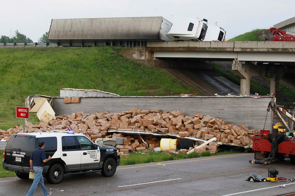 . A semi-tractor trailer (top) rests on its side against the guard rails on Interstate 40 as another trailer lies broken open on the road below after falling from I-40, following a tornado strike near Highway 177 north of Shawnee, Oklahoma May 19,  2013. A tornado half a mile wide struck near Oklahoma City on Sunday, part of a massive storm front that hammered the central United States. News reports said at least one person had died. REUTERS/Bill Waugh