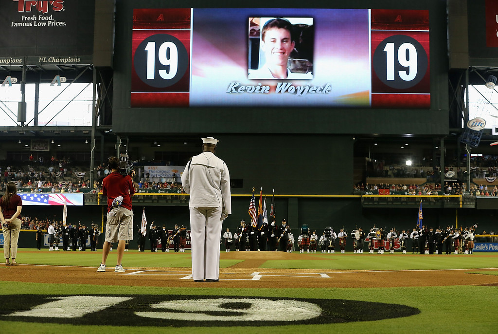 """. PHOENIX, AZ - JULY 05:  The Arizona Diamondbacks honor the 19 Granite Mountain Interagency Hotshot Crew firefighters who died battling a fast-moving wildfire near Yarnell, AZ before the MLB game between the Arizona Diamondbacks and the Colorado Rockies at Chase Field on July 5, 2013 in Phoenix, Arizona. The Arizona Diamondbacks are wearing a \""""19\"""" patch in honor of (Photo by Christian Petersen/Getty Images)"""