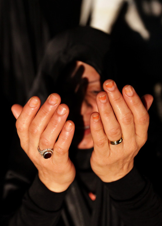 ". A Bahraini woman prays in a street in Malkiya, Bahrain, after participating in call of ""God is Greater\"" that echoed through opposition villages nationwide on Monday night, Aug. 12, 2013. The simultaneous shout-out, similar to what was done in the earlier days of Bahrain\'s 2 1/2-year-old pro-democracy uprising, is meant as a show of opposition solidarity ahead of plans this week to attempt major protests. (AP Photo/Hasan Jamali)"