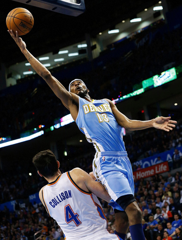 . Denver Nuggets forward Corey Brewer (13) is fouled by Oklahoma City Thunder forward Nick Collison (4) as he shoots in the second quarter of an NBA basketball game in Oklahoma City, Tuesday, March 19, 2013. (AP Photo/Sue Ogrocki)