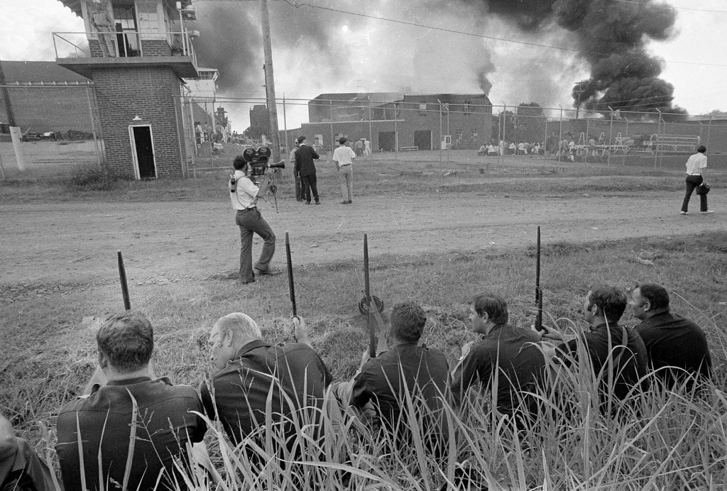 . In this July 28, 1973 black and white file photo, Oklahoma State Highway Patrolmen, foreground, wait their chance for action as they watch flames destroy the shop area at the Oklahoma State Prison at McAlester, Okla. The prison erupted into violence on July 27, 1973, the result of overcrowding, inadequate supervision, poor health care and a culture of violence within the prison walls. (AP Photo/Staff, File)