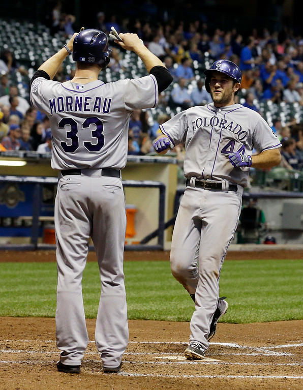 . Colorado Rockies\' Ryan Wheeler is congratulated at home by Justin Morneau (33) after hitting a grand slam during the fourth inning of a baseball game against the Milwaukee Brewers Thursday, June 26, 2014, in Milwaukee. (AP Photo/Morry Gash)