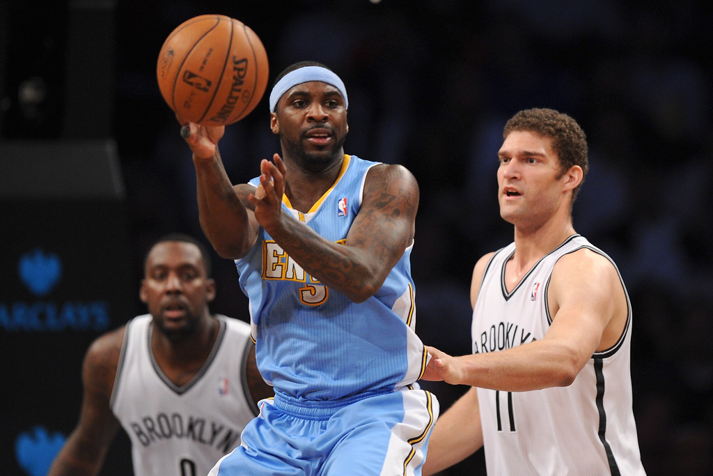 . NEW YORK, NY - DECEMBER 03:  Ty Lawson #3 of the Denver Nuggets looks for a pass with pressure from Brook Lopez #11 of the Brooklyn Nets during the second half at Barclays Center on December 3, 2013 in the Brooklyn borough of New York City. The Nuggets defeat the Nets 111-87. (Photo by Maddie Meyer/Getty Images)