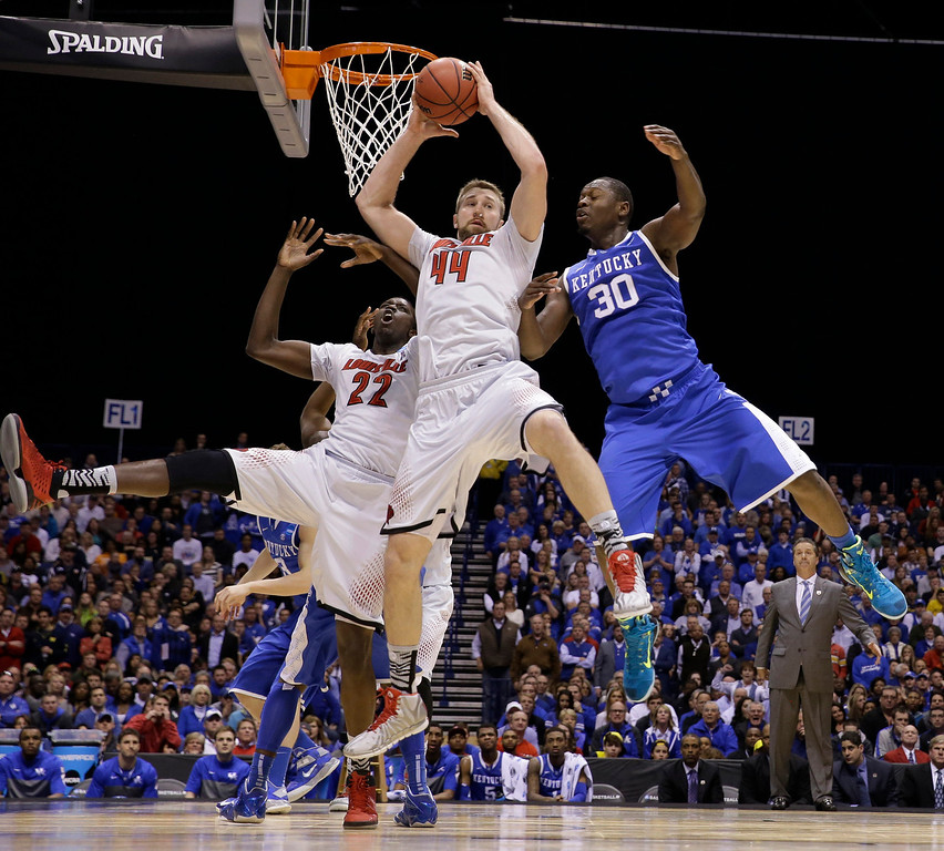 . Louisville\'s Stephan Van Treese grabs a rebound against Kentucky\'s Julius Randle (30) during the first half of an NCAA Midwest Regional semifinal college basketball tournament game against the Kentucky Friday, March 28, 2014, in Indianapolis. At left is Louisville\'s Akoy Agau (22)(AP Photo/David J. Phillip)