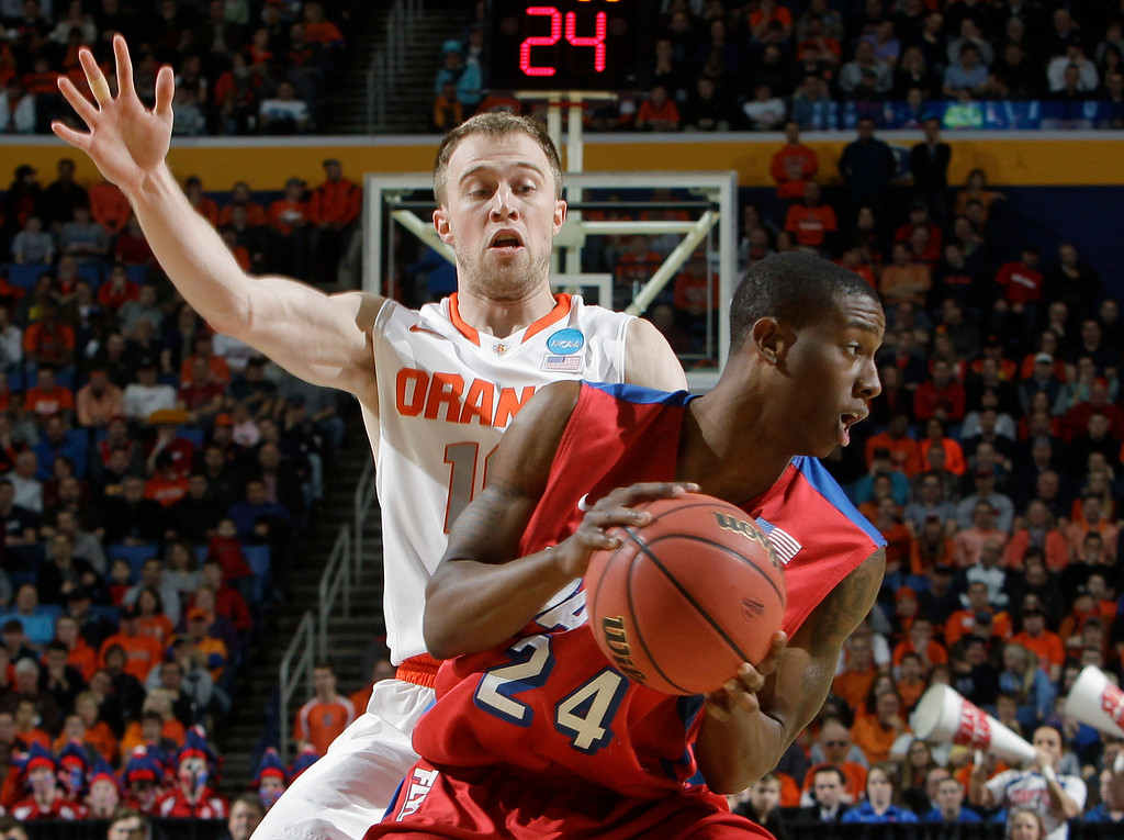 . Syracuse\'s Trevor Cooney, left, defends Dayton\'s Jordan Sibert during the first half of a third-round game in the NCAA men\'s college basketball tournament in Buffalo, N.Y., Saturday, March 22, 2014. (AP Photo/Bill Wippert)