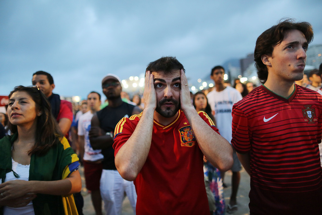 . A soccer fan holds his hands to head as he watches the World Cup match between Chile and Spain inside the FIFA Fan Fest area on Copacabana beach, in Rio de Janeiro, Brazil, Wednesday, June 18, 2014. Chile defeated Spain, the defending champs 2-0. (AP Photo/Leo Correa)