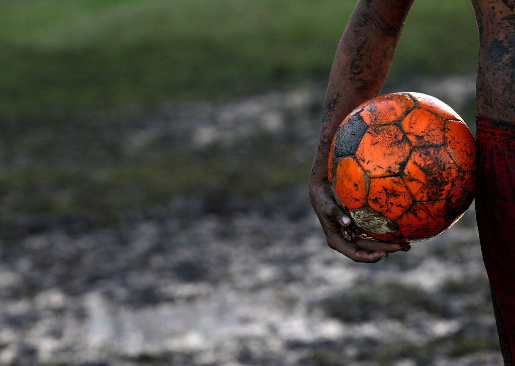 . A Child holds a soccer ball during pick up game of barefoot soccer, in a muddy field in Natal, Brazil, Wednesday, June 18, 2014. Natal is one of the host cities for the World Cup soccer tournament. (AP Photo/Petr David Josek)