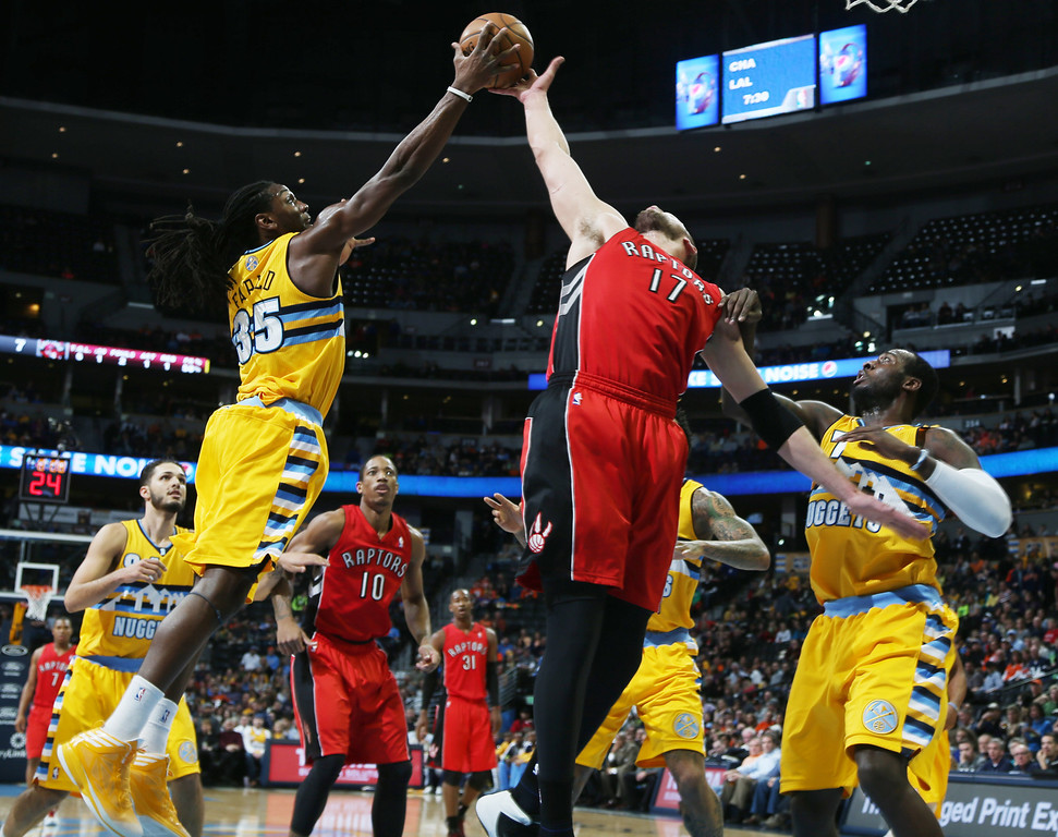 . Denver Nuggets forward Kenneth Faried, left, bats away a rebound from Toronto Raptors center Jonas Valanciunas, of Lithuania, as Nuggets forward J.J. Hickson, right, covers the play in the first quarter of an NBA basketball game in Denver, Friday, Jan. 31, 2014. (AP Photo/David Zalubowski)