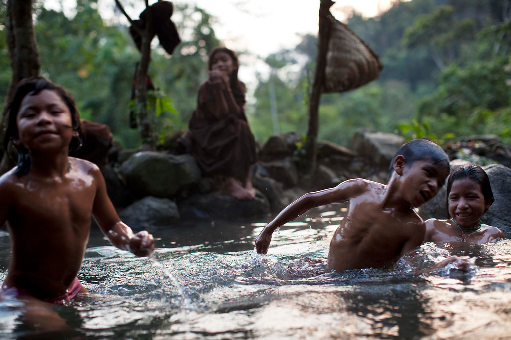 . In this Sept. 30, 2013 photo, Ashaninka Indian children wade in the natural hot springs in Kitamaronkani, Pichari district, Peru. Their world has rarely been peaceful. During Peruís 1980-2000 internal conflict, Shining Path rebels overran their lands and slaughtered them wholesale. The government is now boosting its military footprint in the valley in a bid to fight Shining Path remnants and the drug traffickers they protect. (AP Photo/Rodrigo Abd)