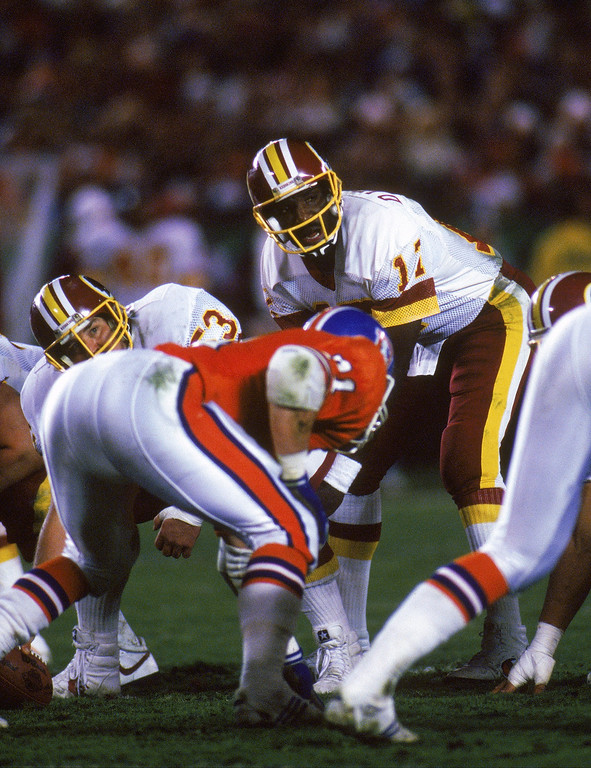 . Quarterback Doug Williams #17 of the Washington Redskins looks to his left as he calls a play at the line of scrimmage during Super Bowl XXII against the Denver Broncos at Jack Murphy Stadium on January 31, 1988 in San Diego, California.  The Redskins won 42-10.  (Photo by Rick Stewart/Getty Images)
