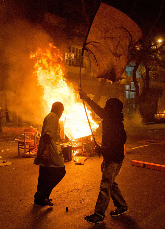 """. Demonstrators remain near a burning barricade after a protest for the \""""Teachers\' day\"""", on October 15, 2013 in Rio de Janeiro, Brazil. AFP PHOTO / CHRISTOPHE SIMON/AFP/Getty Images"""