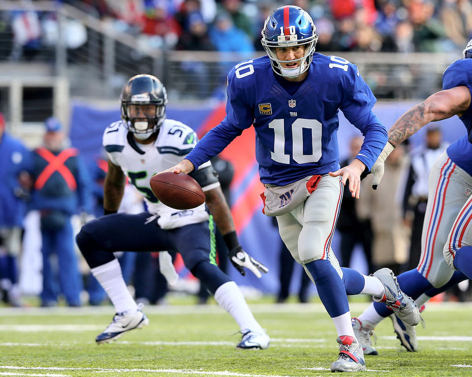 . Eli Manning #10 of the New York Giants scrambles as  Bruce Irvin #51 of the Seattle Seahawks defends at MetLife Stadium on December 15, 2013 in East Rutherford, New Jersey.  (Photo by Elsa/Getty Images)