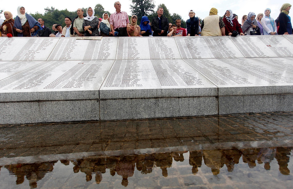 . Bosnians stand behind a memorial plaque, inscribed with the names of victims from the 1995 Srebrenica massacre, before praying in front of 409 coffins of newly identified victims in Potocari Memorial Center, near Srebrenica July 11, 2013. The bodies of the recently identified victims will be buried on July 11 marking the 18th anniversary of the massacre in which Bosnian Serb forces commanded by Ratko Mladic killed up to 8,000 Muslim men and boys and buried them in mass graves. REUTERS/Dado Ruvic