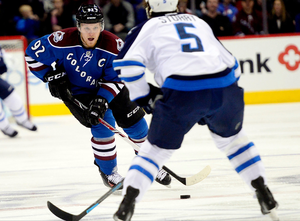 . Gabriel Landeskog (92) of the Colorado Avalanche brings the puck up the ice as Mark Stuart (5) of the Winnipeg Jets defends during the first period of action.  (Photo by AAron Ontiveroz/The Denver Post)