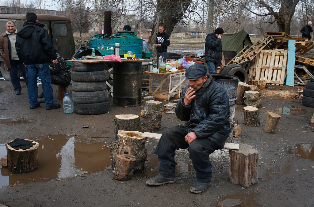. Pro Russian activists camped near the armory of Ukrainian army in a bid to prevent the export of arms and ammunition in the village of Poraskoveyevka, eastern Ukraine, Thursday, March 20, 2014. (AP Photo/Sergei Grits)