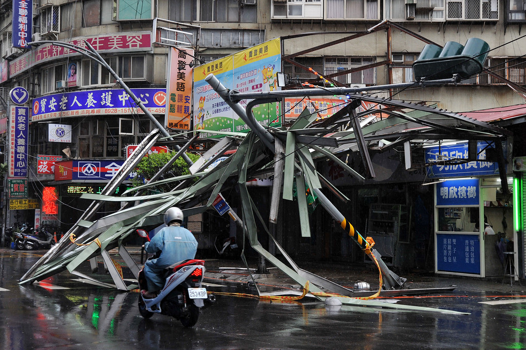 ". A motorcycle drives past a damaged tin roof and traffic signs caused by typhoon Soulik in Taipei on July 13, 2013.  Thousands of people were evacuated in Taiwan and the entire island declared an ""alert zone\"" as Typhoon Soulik made landfall early morning, killing one person and injuring seven. Mandy Cheng/AFP/Getty Images"
