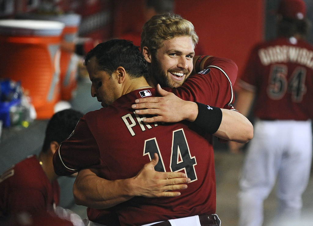 . Infielder Matt Davidson #24 of the Arizona Diamondbacks is hugged by teammate infielder Martin Prado #14 after hitting his first major league career home run against the Colorado Rockies in the fifth inning at Chase Field on September 15, 2013 in Phoenix, Arizona. The Diamondbacks defeated the Rockies 8-2. (Photo by Jennifer Stewart/Getty Images)