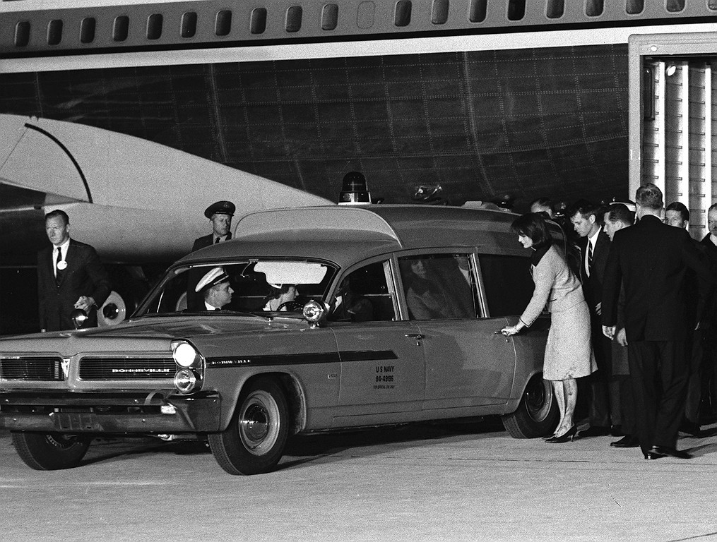 . Her stockings and dress stained with blood, Jacqueline Kennedy reaches for the door of the ambulance carrying  her husband\'s body  at Andrews Air Force Base, Md., on Nov. 22, 1963.  Attorney General Robert F. Kennedy, stands behind the first lady, who had just arrived from Dallas with the body aboard Air Force One.  Associated Press file