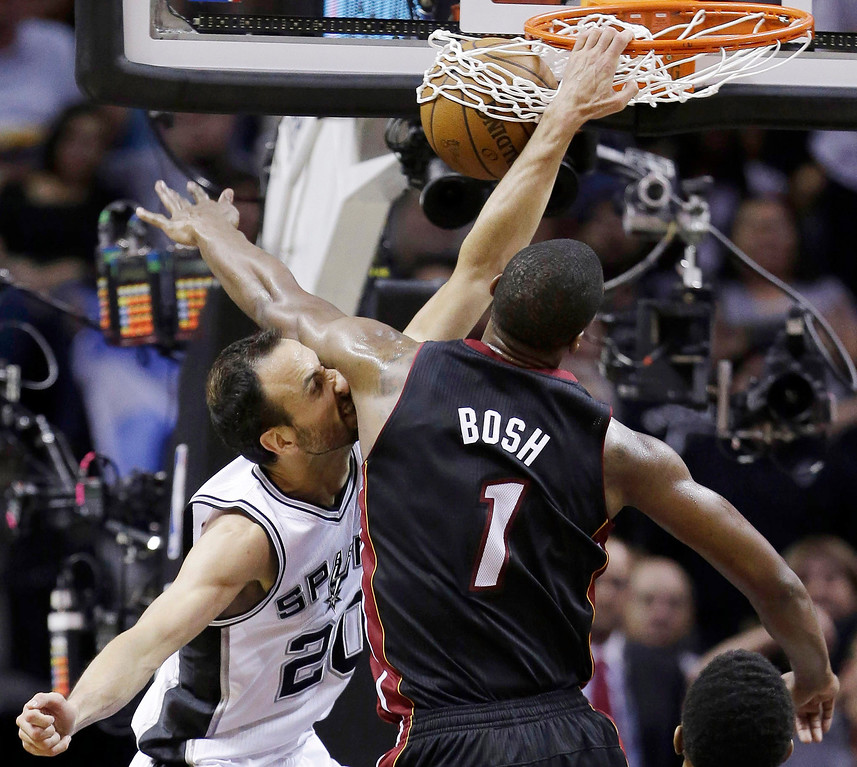 . San Antonio Spurs guard Manu Ginobili (20) dunks as Miami Heat center Chris Bosh (1) defends during the first half in Game 5 of the NBA basketball finals on Sunday, June 15, 2014, in San Antonio. (AP Photo/David J. Phillip)