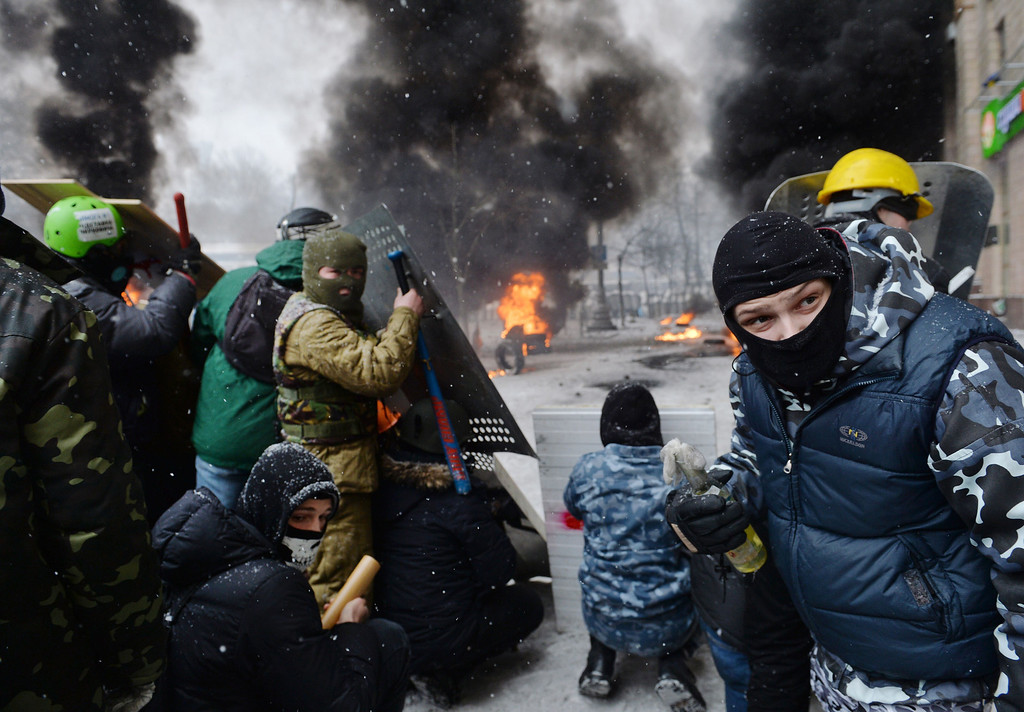 . A demonstrator holds an incendiary device as protesters clash with police in the center of Kiev on January 22, 2014.  AFP PHOTO / SERGEI  SUPINSKY/AFP/Getty Images