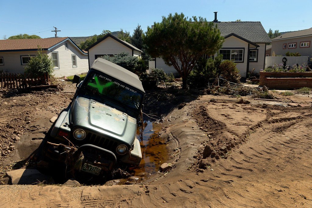 . A jeep rests in a sinkhole in Lyons,  CO September 20, 2013. Friday was the second day residents were allowed to return to their homes.  (Photo By Craig F. Walker / The Denver Post)