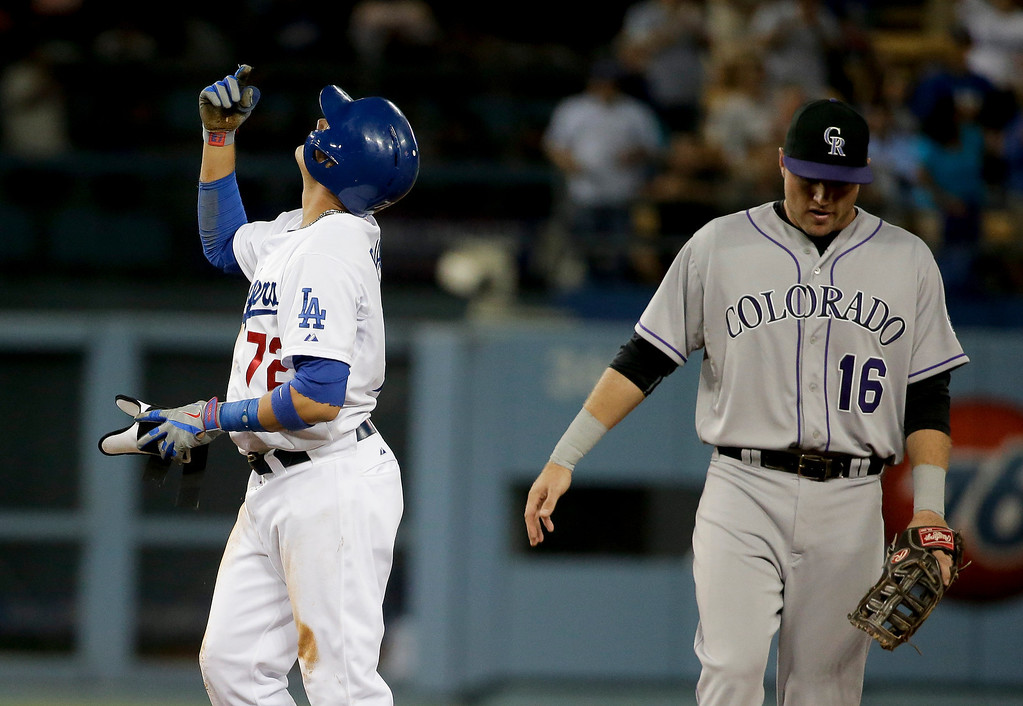 . Los Angeles Dodgers\' Miguel Rojas, left, celebrates his three-run double as Colorado Rockies first baseman Kyle Parker looks away during third inning of a baseball game in Los Angeles, Wednesday, June 18, 2014. (AP Photo/Chris Carlson)