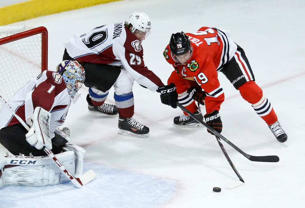 . Colorado Avalanche center Nathan MacKinnon (29) keeps Chicago Blackhawks center Jonathan Toews (19) from getting a shot on goal as goalie Semyon Varlamov defends during the first period of an NHL hockey game Tuesday, Jan. 14, 2014, in Chicago. (AP Photo/Charles Rex Arbogast)