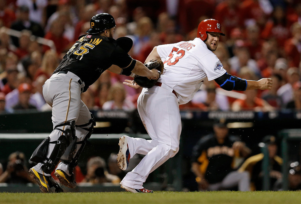. St. Louis Cardinals\' Matt Adams (53) is tagged out by Pittsburgh Pirates\' Russell Martin (55) in the fourth inning of Game 5 of a National League baseball division series on Wednesday, Oct. 9, 2013, in St. Louis. Adams was caught between third and home on a ground ball by Jon Jay. (AP Photo/Jeff Roberson)