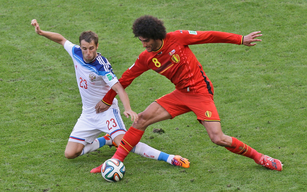 . Russia\'s Dmitry Kombarov, left, and Belgium\'s Marouane Fellaini challenge for the ball during the group H World Cup soccer match between Belgium and Russia at the Maracana Stadium in Rio de Janeiro, Brazil, Sunday, June 22, 2014. (AP Photo/Andrew Medichini)
