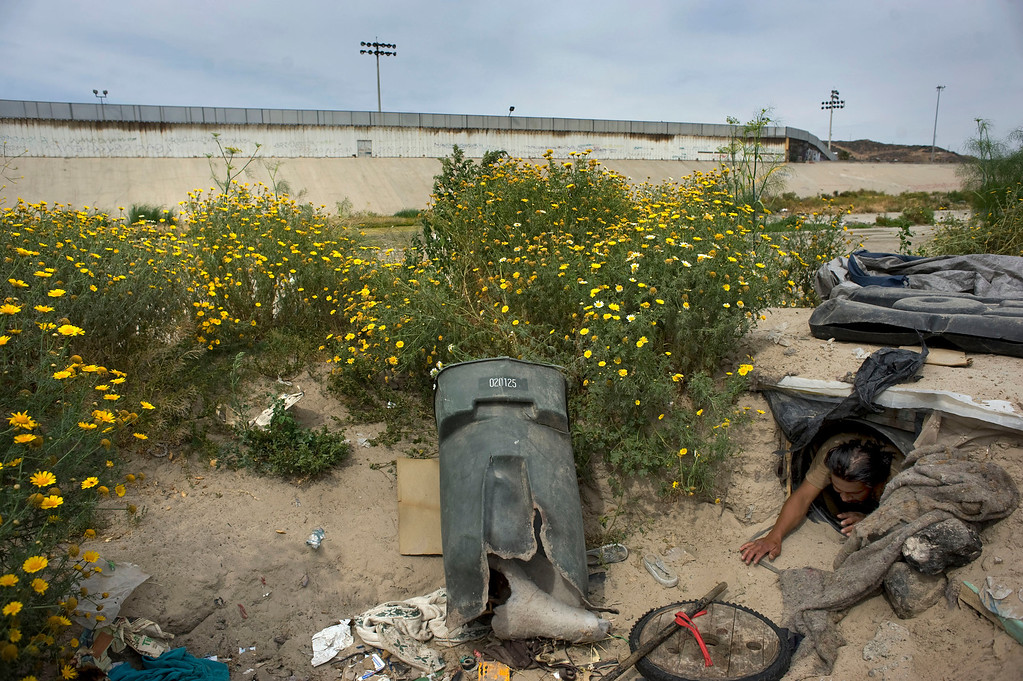 . Jesus Hernandez, 30, shows how he leaves his underground foxhole that he dug out of the river sediment in the Tijuana River canal, which has become home to hundreds of people deported from the US, in Tijuana, Mexico, 03 May 2013. Hernandez had been living undocumented in the US since he was six-years old, but was deported 18 months ago and has since been living in the river canal. Heightened US border security and record numbers of deportations from the US have created a growing population of people who live homeless in Mexican cities that border with the United States. Many had lived for years undocumented in the US and have little or no family and other support in Mexico, and are subject to fall into depression, substance abuse and crime. Tijuana, Mexico, borders on the US city of San Diego, California.  EPA/DAVID MAUNG