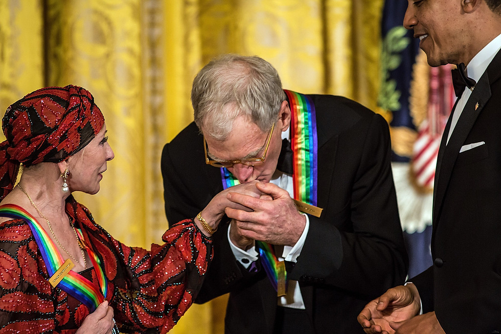 . WASHINGTON - DECEMBER 2: (AFP OUT) Comedian David Letterman kisses the hand of ballerina Natalia Makarova (L) as President Barack Obama (R) looks on at the Kennedy Center Honors reception at the White House on December 2, 2012 in Washington, DC. The Kennedy Center Honors recognized seven individuals - Buddy Guy, Dustin Hoffman, David Letterman, Natalia Makarova, John Paul Jones, Jimmy Page, and Robert Plant - for their lifetime contributions to American culture through the performing arts. (Photo by Brendan Hoffman/Getty Images)
