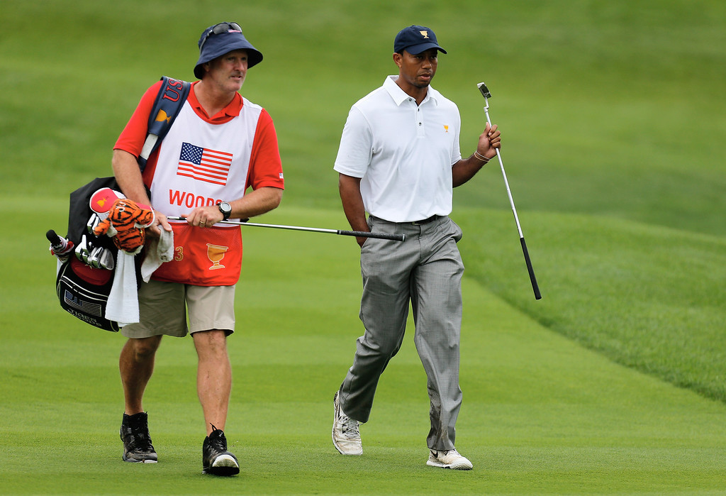 . Tiger Woods of the U.S. Team walks with his caddie Joe LaCava to the 18th greeen during the Day Four Singles Matches at the Muirfield Village Golf Club on October 6, 2013  in Dublin, Ohio.  (Photo by Gregory Shamus/Getty Images)