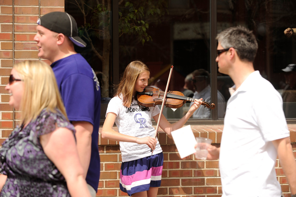 . Hannah Hayden plays the fiddle as fans file towards the stadium on Blake Street. (Photo by Karl Gehring/The Denver Post)