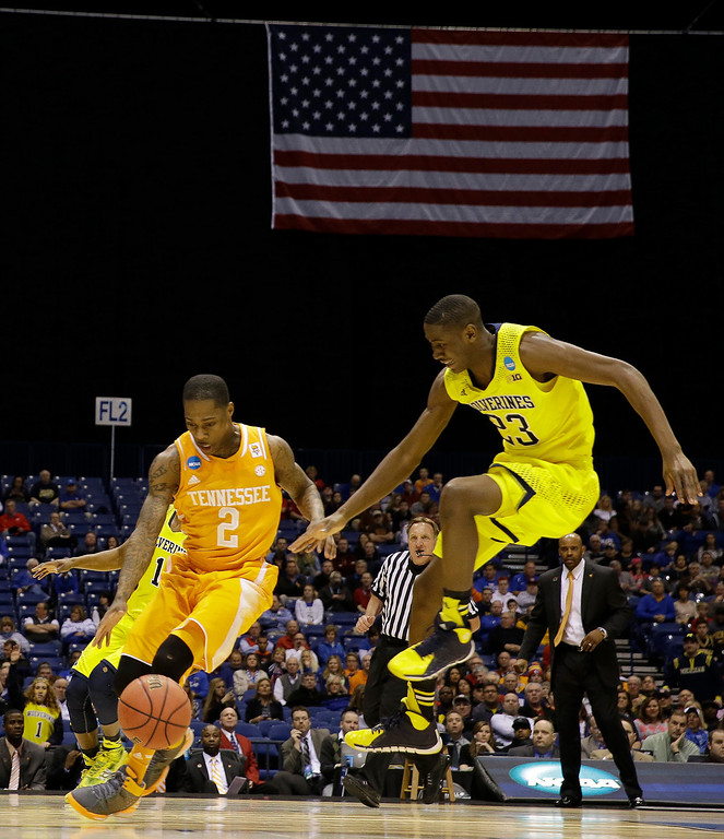 . Tennessee\'s Antonio Barton (2) and Michigan\'s Caris LeVert (23) go after a loose ball during the first half of an NCAA Midwest Regional semifinal college basketball tournament game Friday, March 28, 2014, in Indianapolis. (AP Photo/David J. Phillip)