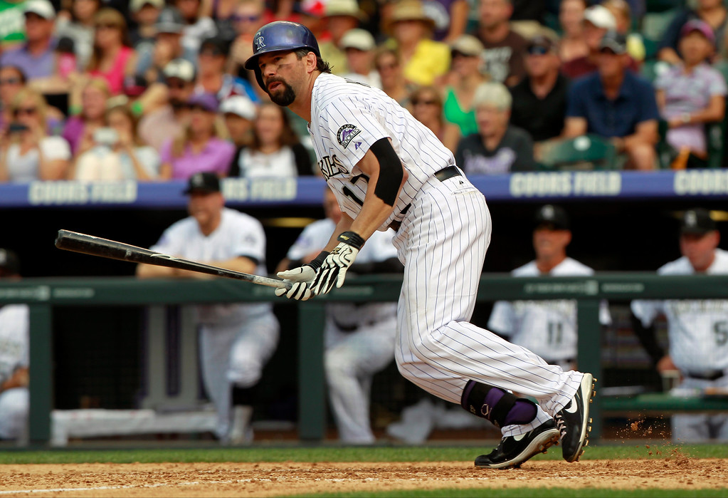 . Colorado Rockies\' Todd Helton follows the flight of his double against the Cincinnati Reds in the seventh inning of a baseball game in Denver on Sunday, Sept. 1, 2013. The hit was the 2,500th in Helton\'s career. (AP Photo/David Zalubowski)
