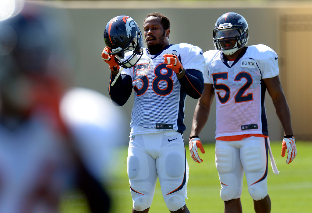 . Denver Broncos outside linebacker Von Miller (58) puts on his helmet during practice August 20, 2013 at Dove Valley. The discipline of the Broncos\' star linebacker are expected to continue Tuesday. (Photo by John Leyba/The Denver Post)