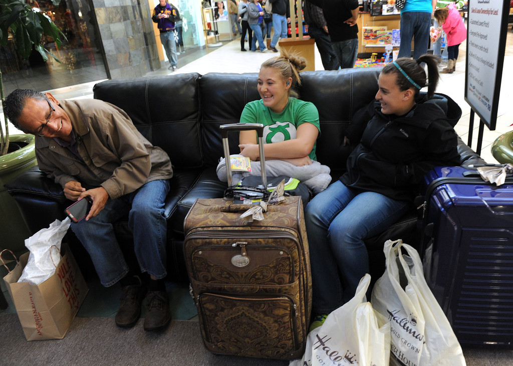 . Jessie Morales, left, chats with Chelsea Lamb, center, and Sarah Andrews, right, after shopping for Black Friday deals at the Mall of Abilene Friday, Nov. 29, 2013, in Abilene, Texas.  Lamb\'s aunt bought the suitcases and the girls filled them up with several of their own purchases. (AP Photo/Abilene Reporter-News, Nellie Doneva)