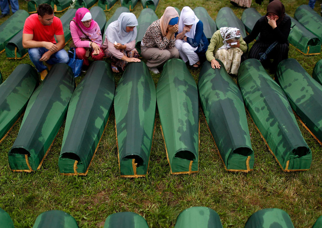. Bosnian woman cry beside coffins of relatives, which are amongst the 409 coffins of newly identified victims of the 1995 Srebrenica massacre, in Potocari Memorial Center, near Srebrenica July 11, 2013. The bodies of the recently identified victims will be transported to the memorial centre in Potocari where they will be buried on July 11 marking the 18th anniversary of the massacre in which Bosnian Serb forces commanded by Ratko Mladic killed up to 8,000 Muslim men and boys and buried them in mass graves. REUTERS/Dado Ruvic