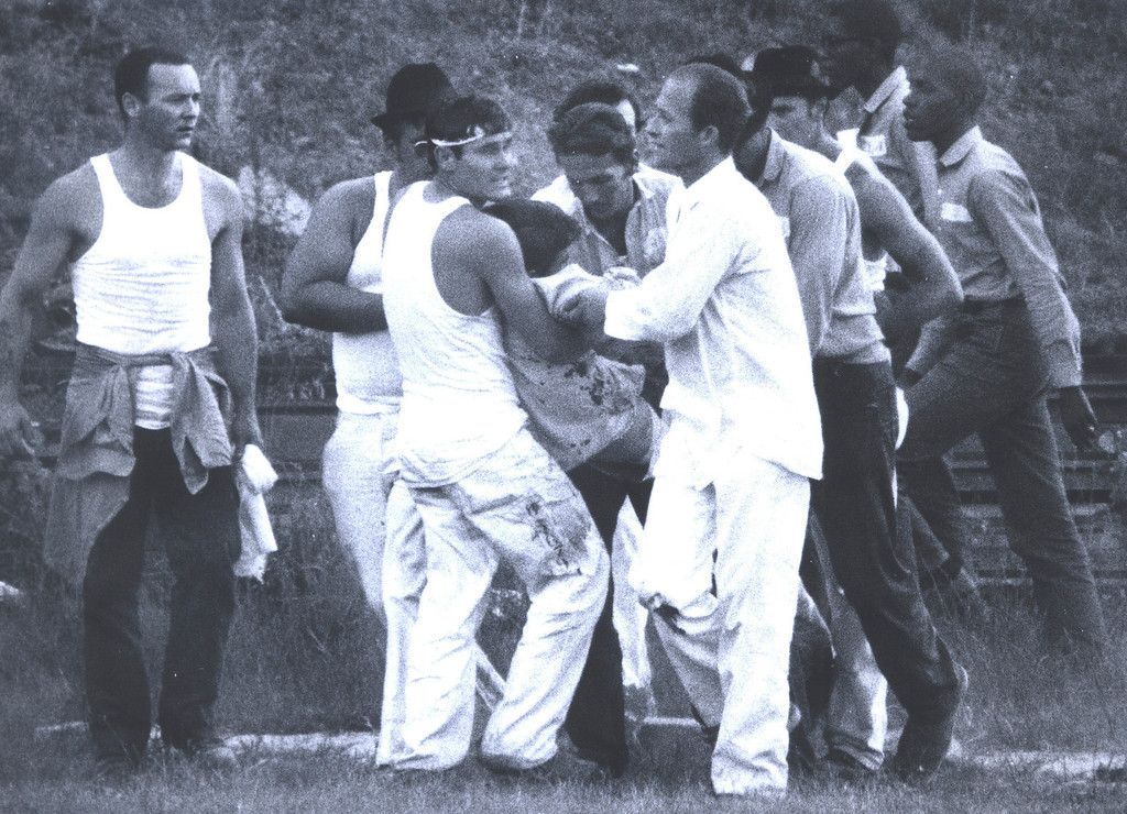 . In this July 1973 photo provided by the Oklahoma Department of Corrections, inmates carry a wounded inmate at the Oklahoma State Penitentiary at McAlester in McAlester, Okla. during one of the most destructive prison riots in American history. (AP Photo/Oklahoma Department of Corrections)