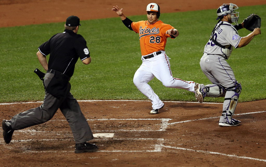 . BALTIMORE, MD - AUGUST 17: Steve Pearce #28 of the Baltimore Orioles scores a run in front of catcher Wilin Rosario #20 of the Colorado Rockies and home plate umpire Chris Conroy during the third inning at Oriole Park at Camden Yards on August 17, 2013 in Baltimore, Maryland.  (Photo by Rob Carr/Getty Images)