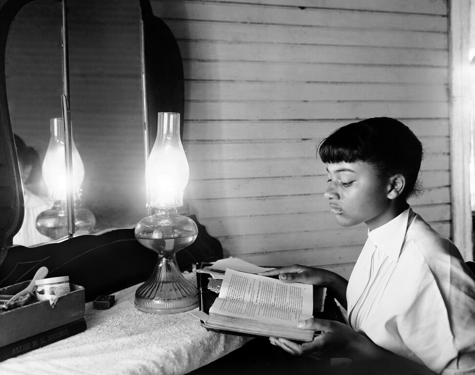 """. By the light of a kerosene lamp, 14-year-old Henrietta Hilton studies in her tenant farm home in Summerton, S.C., on June 4, 1954. She is in the ninth grade. Discussing the Supreme Court decision against school segregation, Henrietta says: \""""I\'d like to go to school with white children... I think I\'d enjoy being friends with some white girls. Maybe they\'d enjoy being friends with me.\"""" (AP Photo/Rudolph Faircloth)"""