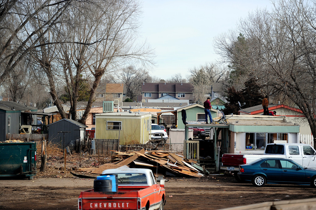 . MILLIKEN, CO - DECEMBER 18: Volunteers help Jose Moreno as he deconstructs his home at the Evergreen Mobile Home Park. Residents of the mobile home park say that the city of Milliken has not done enough to assist in the rebuilding of the 33-unit residential sub division that was struck hard by recent floods that ravaged much of northern Colorado. (Photo by AAron Ontiveroz/The Denver Post)
