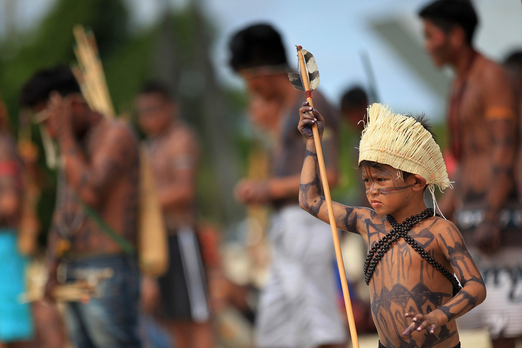 . A Brazilian Munduruku Indian boy stands with others as they try to enter the Planalto Palace during a protest in Brasilia June 6, 2013. They are demonstrating against violations of indigenous rights and calling for the suspension of the construction of the Belo Monte hydroelectric plant on the Xingu river, a huge project aimed at feeding Brazil\'s fast-growing demand for electricity. REUTERS/Ueslei Marcelino