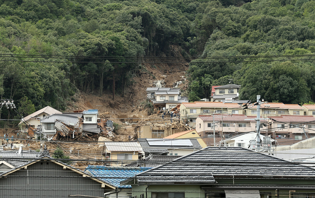 . Rescue workers at the site of a landslide in a residential area on August 20, 2014 in Hiroshima, Japan. (Photo by Buddhika Weerasinghe/Getty Images)