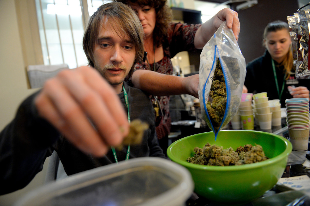 . NORTHGLENN, CO. - DECEMBER 31: Skyler Hall weighs grams of marijuana while Cheri Hackett replenishes his supply at BotanaCare 21+ in Northglenn, CO December 31, 2013. The retail marijuana center was preparing to open at 9am on January 1, 2014 when Colorado becomes the first place anywhere in the world to allow legal marijuana sales to anybody over 21 for any purpose. (Photo By Craig F. Walker / The Denver Post)