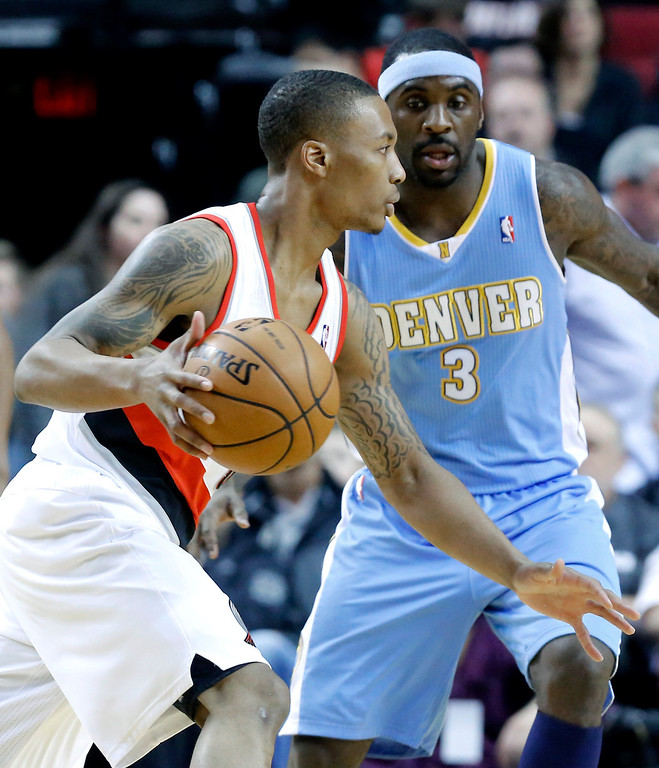 . Portland Trail Blazers guard Damian Lillard, left, drives against Denver Nuggets guard Ty Lawson during the first quarter of an NBA basketball game in Portland, Ore., Thursday, Dec. 20, 2012. (AP Photo/Don Ryan)