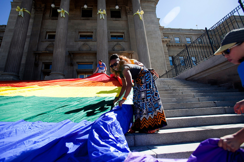 . Chanel DaSilva, center, helps unroll a large rainbow flag on the steps of the Idaho state Capitol during the Boise Gay Pride celebration on Saturday, June 15, 2013, in Boise, Idaho. (AP Photo/The Idaho Statesman, Kyle Green)