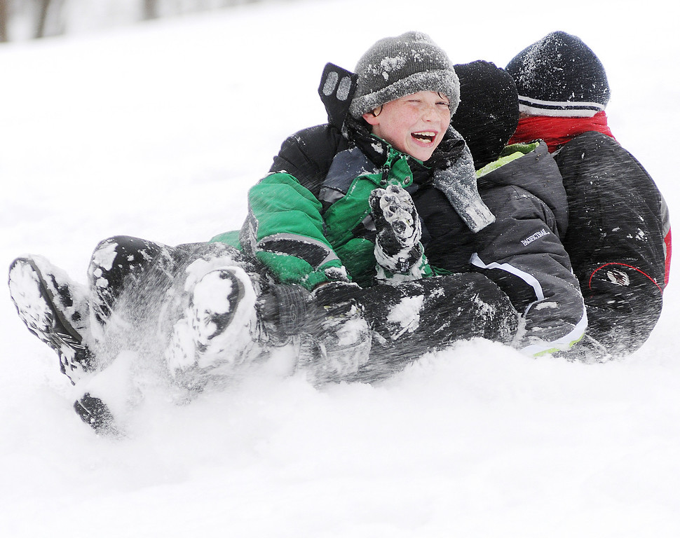 . From left, Daniel Meier, 11, Matthew Thorn, 11, and Logan Smith, 12 all of Winona, Minn., share a sled while sledding down the hill at Bluffside Park Thursday, Dec. 20, 2012, in Winona, Minn. (AP Photo/Winona Daily News, Joe Ahlquist)