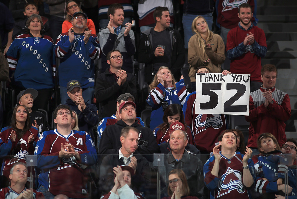 . DENVER, CO - NOVEMBER 02:  Fans applaud and display signs as the jersey of retired player Adam Foote #52 of the Colorado Avalanche is hoisted to the rafters as his number was retired in a pregame ceremony prior to facing the Montreal Canadiens at Pepsi Center on November 2, 2013 in Denver, Colorado.  (Photo by Doug Pensinger/Getty Images)