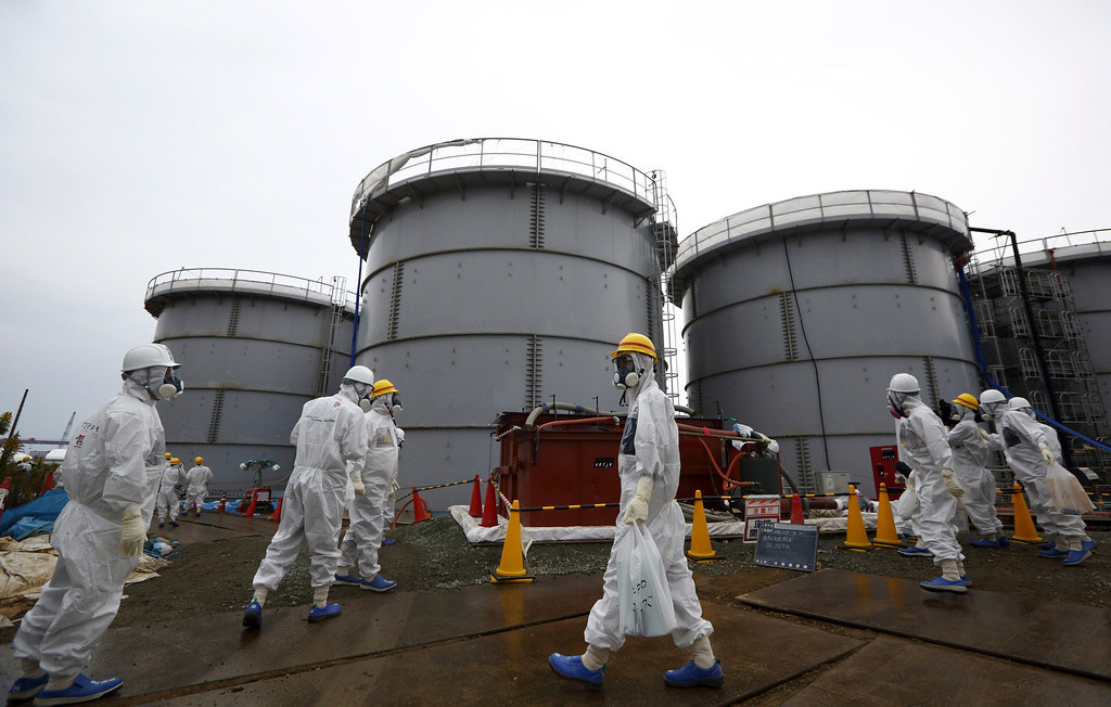 . Members of the media and Tokyo Electric Power Co. employees wearing protective suits and masks walk past storage tanks for radioactive water in the H4 area at the Fukushima Dai-ichi nuclear power plant in Okuma, Fukushima, northeastern Japan, Thursday, Nov. 7, 2013.  (AP Photo/Tomohiro Ohsumi, Pool)
